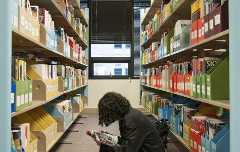 Student reads a magazine in the library. Advocate File Photo