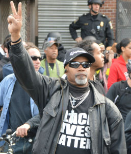 Tuesday ,April 28: Baltimore Protester Holding Up the Peace Sign (Photo Credit: Peter Langer)
