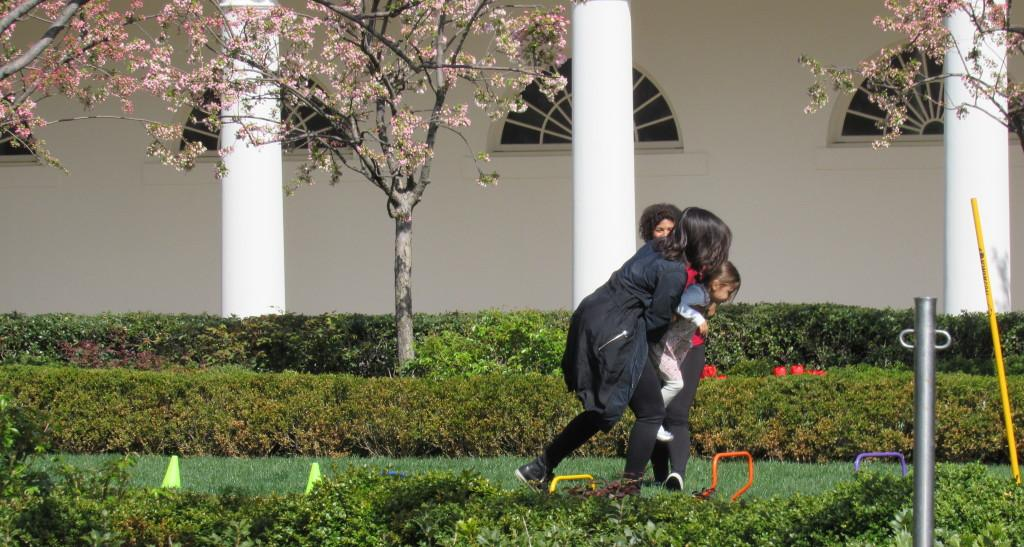Michelle Obama helping to carry a little boy to the end of the obstacle course photo: Sara Monterroso)