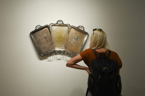A student views one of Jaydan Moore's found platter artworks.
