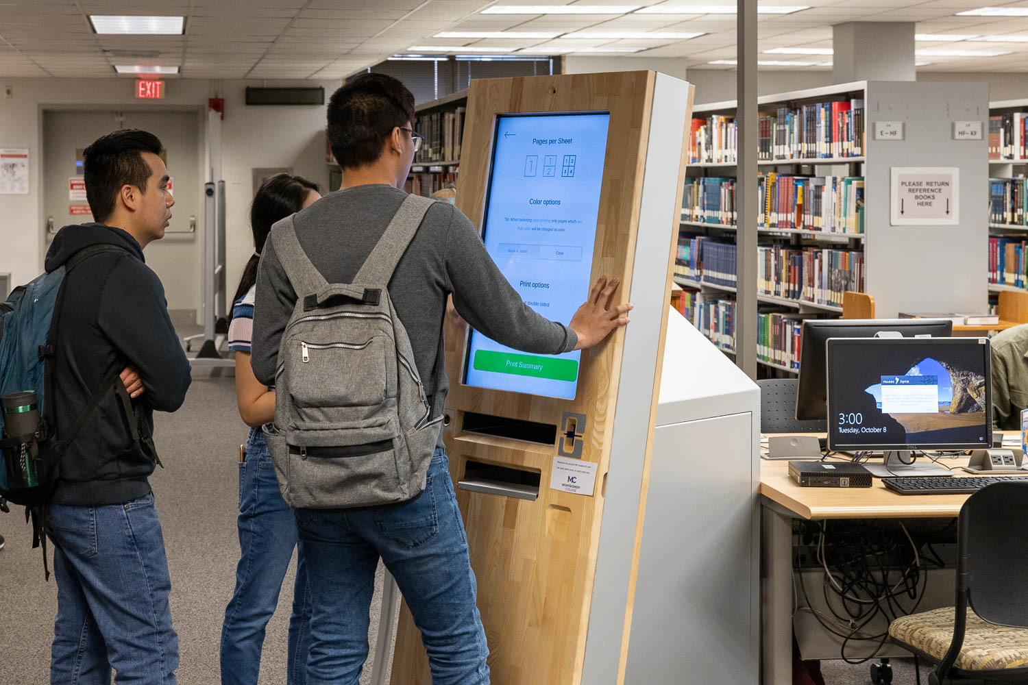 Students using the printer located in the library.