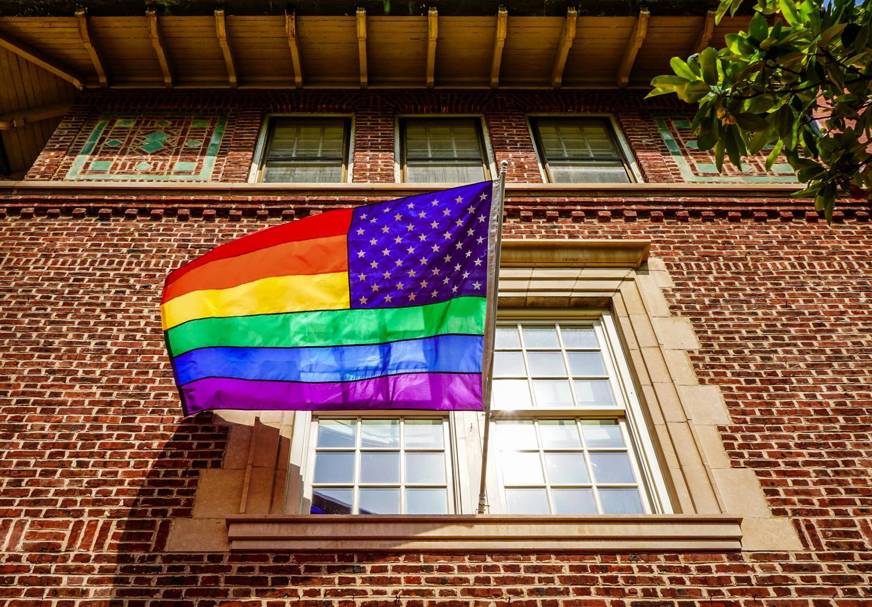 Pride/USA flag peeking from window in Washigton, DC via Flickr.