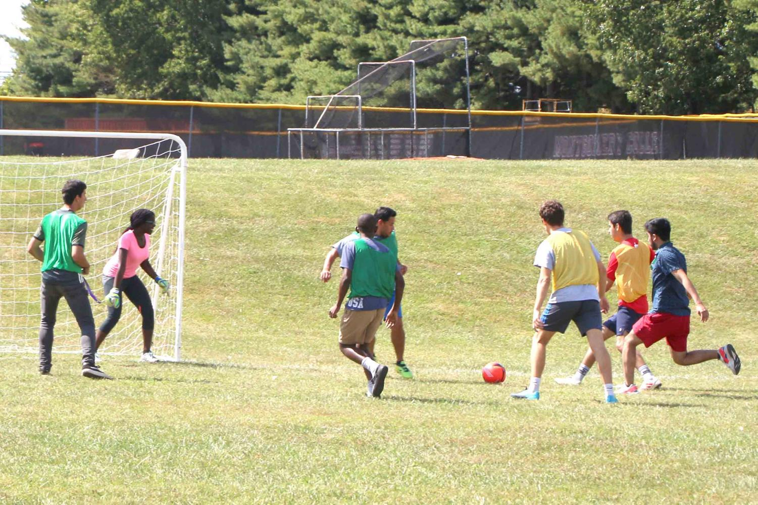 Students attacking for the ball during a friendly green vs. yellow match.